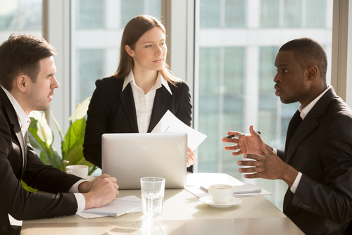 business dispute, a business woman and two men discussing business at a table